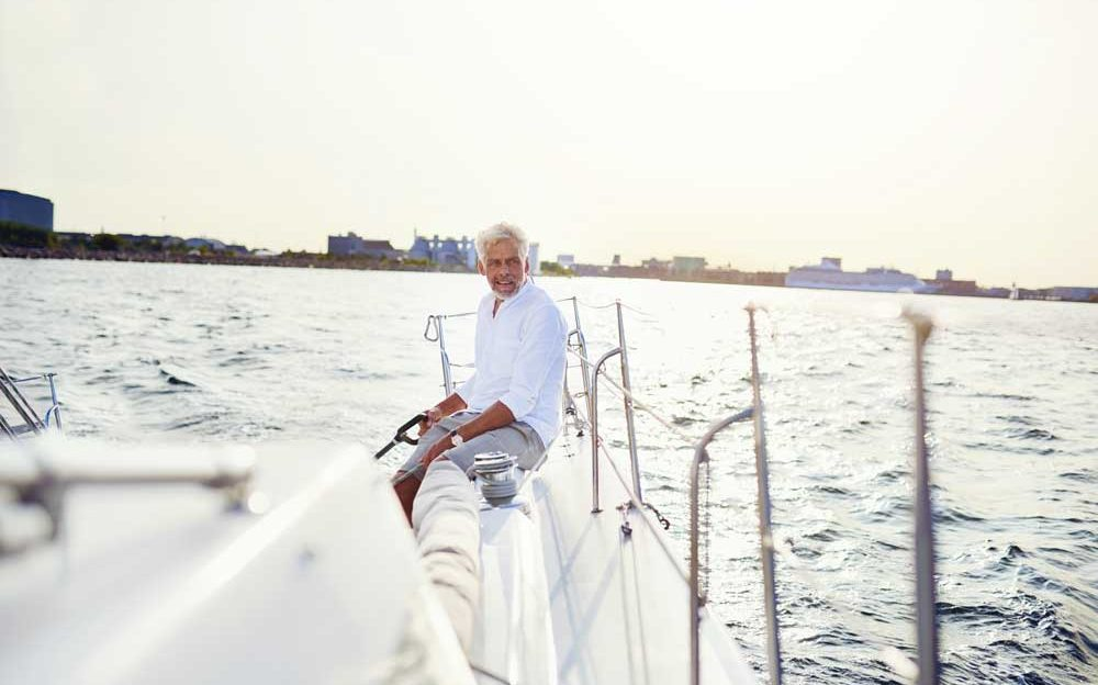 mature-man-out-sailing-his-yacht-on-a-sunny-GXB95PE