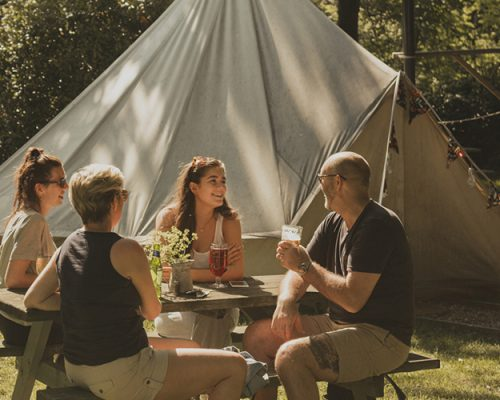 Family of four are sitting at a picnic bench next to their glamping tent. They are all talking and enjoying an alcoholic beverage.