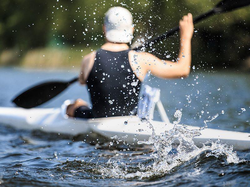 athlete at rowing kayak on lake during competition.splashing water in foreground