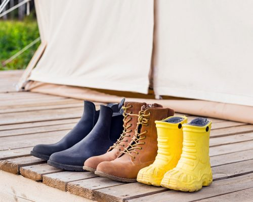 Three pair of shoes near canvas bell tent. Family trip concept
